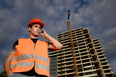 Construction supervisor. In safety helmet and reflex vest with mobile phone in front of construction site Stock Images