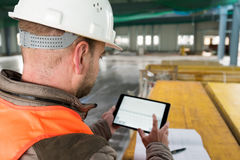 Construction supervisor with digital tablet on site Royalty Free Stock Image