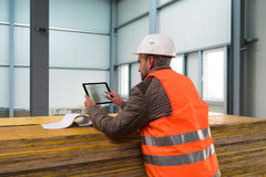 Construction supervisor with digital tablet on site. Construction supervisor checks the interior of a new warehouse being constructed with digital tablets in his royalty free stock photography