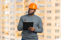 Construction supervisor writes on clipboard. Handsome engineer with black clipboard on blurred background Stock Image