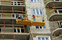 Construction suspended cradle with workers on a newly built high-rise building. Construction suspended yellow cradle with workers on a newly built high-rise Stock Photos
