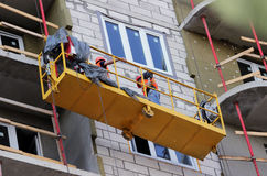 Construction suspended cradle with workers on a newly built high-rise building. Construction suspended yellow cradle with workers on a newly built high-rise Royalty Free Stock Photography