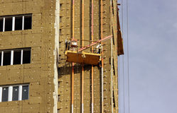 Construction suspended yellow cradle with workers on a newly built high-rise building Stock Photos