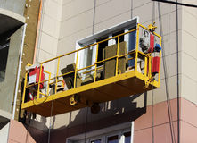 Construction suspended yellow cradle without workers on a newly built high-rise building Stock Photos