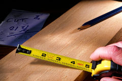 Construction Tape Measure in Carpenter Hand Royalty Free Stock Photography