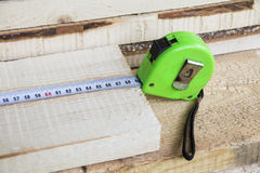 The construction tape measure rests on wooden boards. Construction, repair Royalty Free Stock Photography