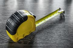 Construction tape measure on wooden board Stock Photos