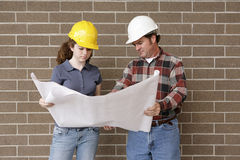 Construction Team with Bluepri. A construction foreman going over blueprints with a female apprentice stock image