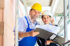 Construction Team with building plans on site. Team or architect and builder or worker with helmets controlling or discuss  construction plan or blueprints of Stock Photo