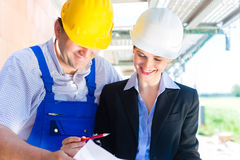 Construction Team with building plans on site Stock Photography