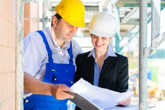 Construction Team with building plans on site Royalty Free Stock Images