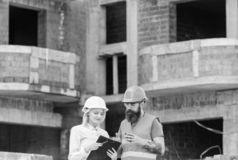 Construction team communication concept. Relationships between construction clients and participants building industry. Discussing plan. Woman engineer and royalty free stock photography
