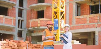 Construction team communication concept. Relationships between construction clients and participants building industry. Woman engineer and brutal builder royalty free stock photo