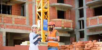 Construction team communication concept. Relationships between construction clients and participants building industry. Woman engineer and brutal builder royalty free stock images
