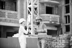 Construction team communication concept. Relationships between construction clients and participants of building. Industry. Woman engineer and brutal builder royalty free stock photography
