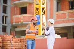 Construction team communication concept. Relationships between construction clients and participants of building. Industry. Woman engineer and brutal builder stock photography