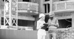 Construction team communication concept. Relationships between construction clients and participants building industry. Woman engineer and builder communicate stock images