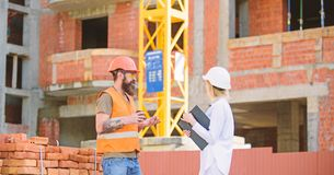Construction team communication concept. Woman engineer and brutal builder communicate construction site background stock photo
