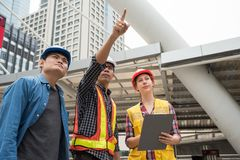 Construction team look at construction site. In town while Asian engieering male manager point finger to it. International joint venture to work in city for Royalty Free Stock Image