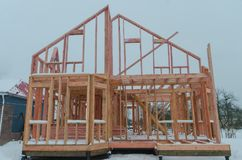 Construction of wooden frame house in winter. Construction of a timber frame house on piles royalty free stock photo