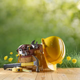 Construction tool and helmet on green nature background. Construction tool and helmet and grass on green nature background Stock Photography