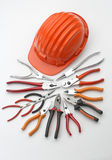 Hard hat with pliers and tongs. An orange hard hat with a series of pliers, side cutters and tongs royalty free stock photo