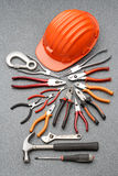 Safety helmet and tools. A safety helmet with different hand tools royalty free stock images