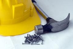 Construction tools. Some builders' tools - a hammer, nails and a yellow safety-gear Stock Image