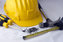Construction tools. Some builders' tools - a hammer, a screwdriver, a measuring tape, nails and a yellow safety-gear Stock Photo