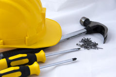 Construction tools. Some builders' tools - a hammer, two screwdrivers, nails and a yellow safety-gear Stock Images