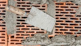 Construction tools close-up, trowel and putty knife with bricks and mortar and cement Royalty Free Stock Image