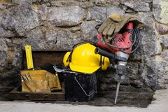 Free Construction Tools For Building A House On A Stone Wall. Hammer, Helmet, And Other Necessary Tools For Construction Or Splitting. Royalty Free Stock Image - 104508956