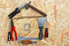 Construction tools in the form of house on wooden background. Royalty Free Stock Image
