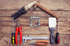 Construction tools in the form of house on wooden background. Royalty Free Stock Images