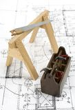 Construction tools on house plans. Closeup image of miniature carpentry tools on house plans royalty free stock photo