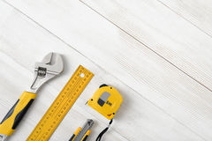Construction tools including centimeter ruler, wrench and cutter placed in the right down corner on wooden surface with Stock Photos