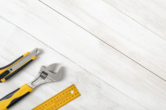 Construction tools including centimeter ruler, wrench and cutter placed in the right down corner on wooden surface with Royalty Free Stock Images
