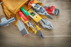 Construction tools in leather toolbelt on wood board.  Royalty Free Stock Photography