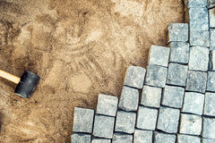 Construction tools, pavement installing and rocks. Granite stones laying on sand, making of pavement Royalty Free Stock Images
