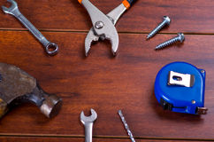 Construction tools, Pliers, hammer, tape measure, screw, flat wrenches, on wooden background Stock Images