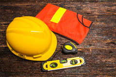Construction tools or safety equipment with yellow helmet on woo Stock Image