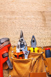 Construction tools in toolbelt monkey wrench. Nippers cutter pliers on wooden board Royalty Free Stock Photo