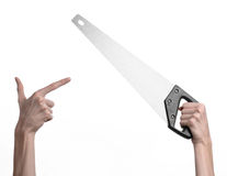 Construction topic: hand holding a saw with a black pen on a white background isolated Royalty Free Stock Photo