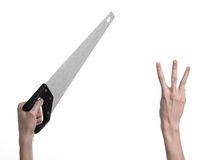 Construction topic: hand holding a saw with a black pen on a white background isolated Royalty Free Stock Image
