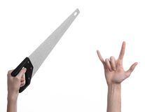 Construction topic: hand holding a saw with a black pen on a white background isolated Stock Photos