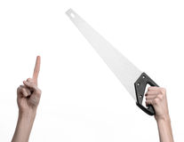 Construction topic: hand holding a saw with a black pen on a white background isolated Stock Images