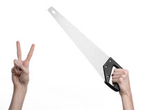 Construction topic: hand holding a saw with a black pen on a white background isolated Royalty Free Stock Photography