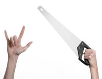 Construction topic: hand holding a saw with a black pen on a white background isolated Royalty Free Stock Images