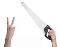 Construction topic: hand holding a saw with a black pen on a white background isolated Stock Image