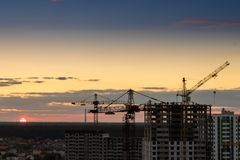 Construction tower crane,Industrial construction cranes on amazing sunset sky background. Crane,Construction tower crane equipment over building construction stock image